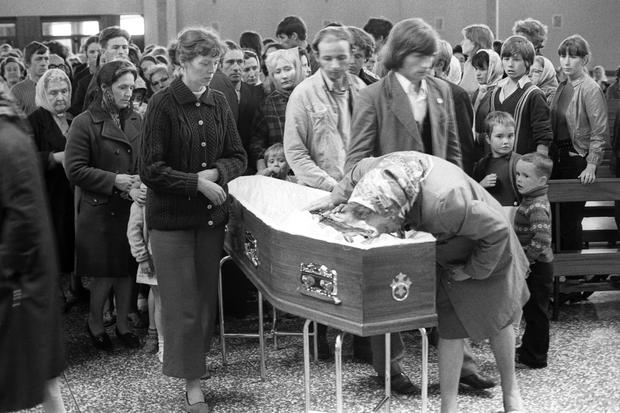 Mourners file past the coffin of Father Hugh Mullan, one of the 10 people killed (PA Archive)