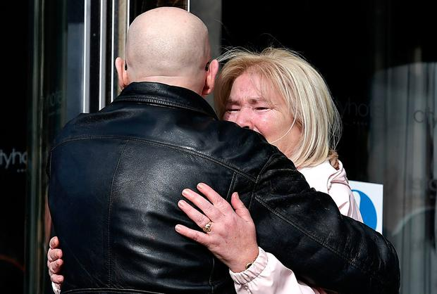 Linda Nash, whose brother William Nash was killed, is comforted by Eamonn McCann