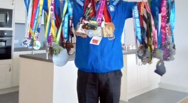 Eugene 'Oggie' Winters shows off some of his medals from his marathon running exploits
