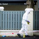 A forensic officer at the scene of the deaths outside the Greenvale Hotel