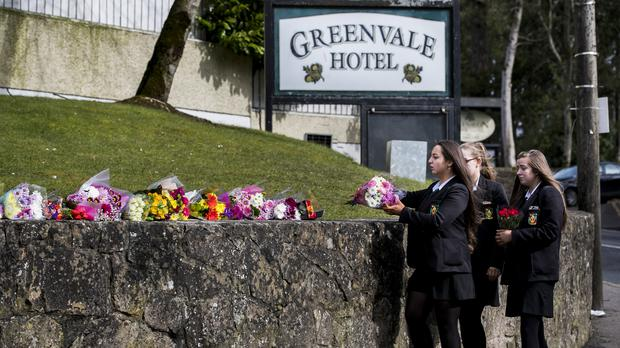 Students from Holy Trinity College leave floral tributes outside The Greenvale Hotel in Cookstown, Co. Tyrone, in Northern Ireland following the deaths of three teenagers, Lauren Bullock, Connor Currie, and Morgan Barnard, at a St Patrick's Day party.