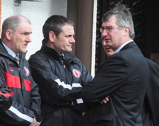 Tom Elliott with Tyrone GAA manager Mickey Harte (left) at the funeral of murdered police officer Ronan Kerr