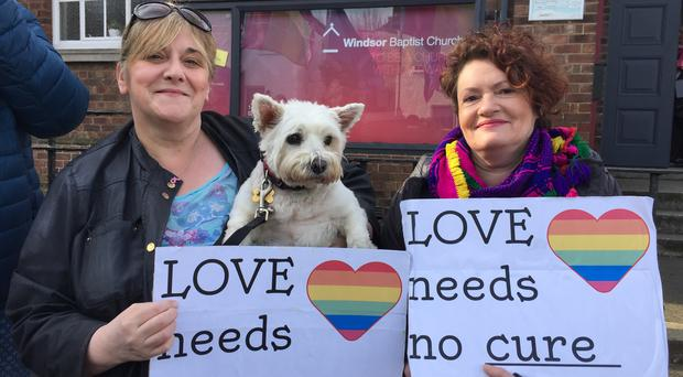 Shirley McPherson, left, her dog Molly, and Helen Crickard protest outside Windsor Baptist Church in Belfast (David Young/PA)