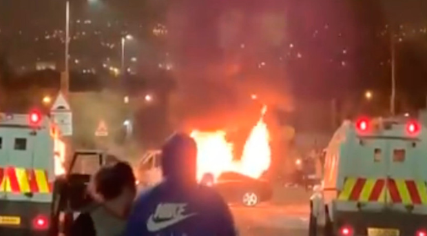 Police Land Rovers parked in front of a burning hijacked car