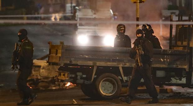 Heavilly armed police guard a crime scene during unrest in Londonderry (Niall Carson/PA)