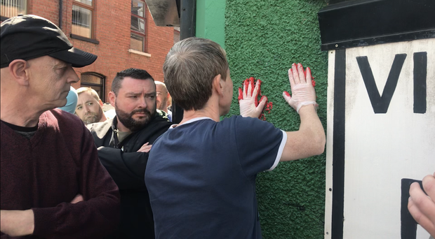 Friends of murdered journalist Lyra McKee deface the walls of a dissident republican office in Derry with red paint (Cate McCurry/PA)