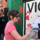 A woman defaces the wall of Saoradh's office in Londonderry