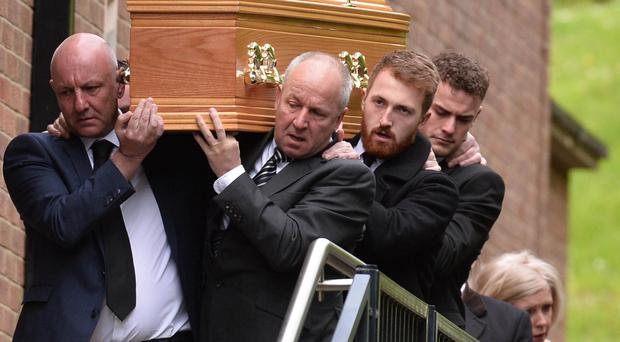 The coffin of Niall Magee is carried out of St Gerard's Church after his funeral service