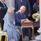 Charles and Camilla sign the visitors' book at Castle Coole yesterday