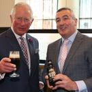 The Prince of Wales has a glass of Belfast Black with Bernard Sloan of Whitewater Brewery at the Grand Central Hotel (Liam McBurney/PA)