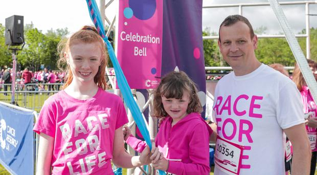 Bangor girls Harriet (13), Genevieve Graham (6) and their father Peter ring the bell to start this year's Cancer Research UK's Race for Life at Stormont estate yesterday