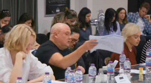 An annoyed looking Conleth Hill, sitting beside Lena Headey and Emilia Clarke, puts script down