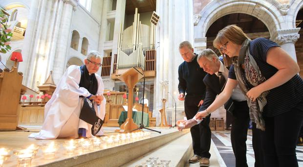 Nikki and Brian Coles light a candle, watched on by Archdeacon Stephen Forde, following special service in St Anne's Cathedral