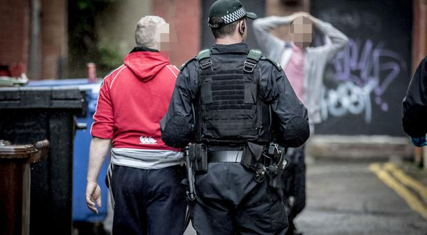 Police with a suspected drug user at College Street Mews in Belfast
