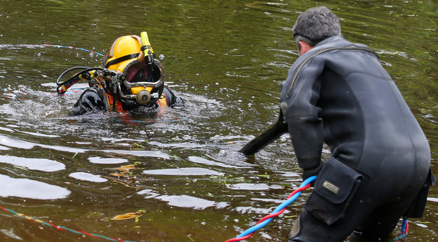 Police divers conduct an underwater search for William 'Pat' McCormick