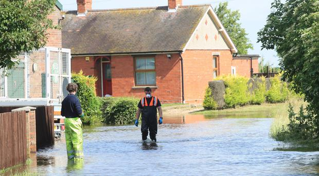 Two men walk through floodwater in Wainfleet in Lincolnshire (Danny Lawson/PA)