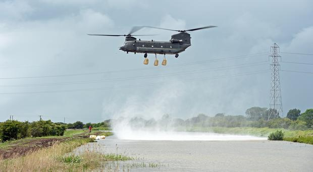 An RAF Chinook helicopter delivers sandbags to plug a gap where the River Steeping burst its banks near Wainfleet All Saints, in Lincolnshire (Joe Giddens/PA)