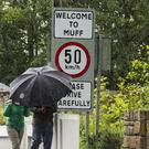 A couple shelter from heavy rain as they walk towards the UK border leaving the Donegal town of Muff in the Republic of Ireland (Liam McBurney/PA)