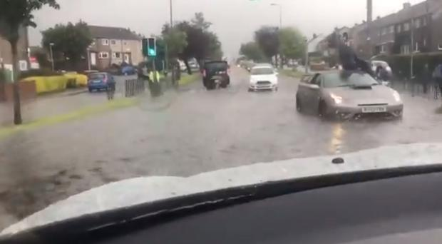 A man sitting on the roof of his car after becoming stranded following flash flooding in Edinburgh (Danielle Mclean/PA)
