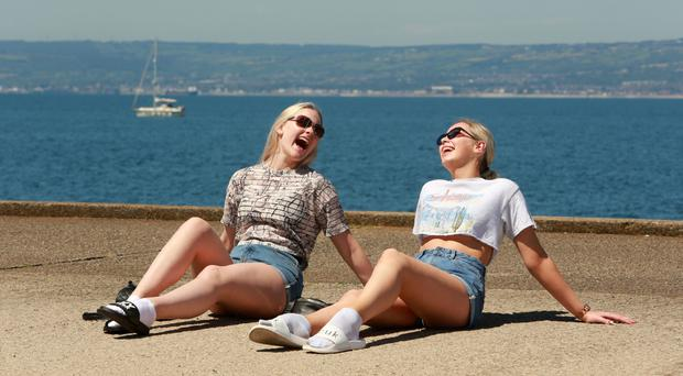Niamh Smith and Emilee Warren from Hertfordshire enjoy the hot weather in Bangor, Co Down, yesterday