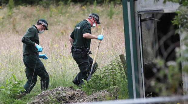 PSNI officers search a field beside a bungalow on the Magherascouse Road, Ballygowan