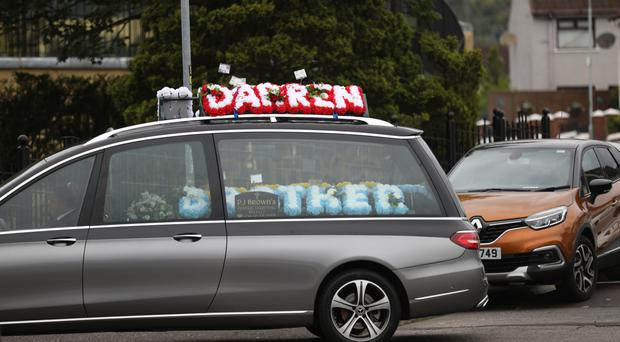 The hearse arrives for the funeral of Darren O'Neill at Holy Trinity Church in Turf Lodge