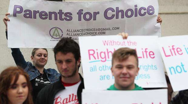 Pro-choice and anti-abortion campaigners outside the Royal Courts of Justice, Belfast (Brian Lawless/PA)