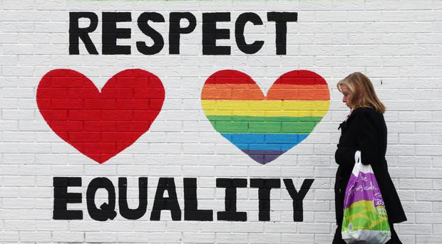 A woman passes a mural in support of same-sex marriage