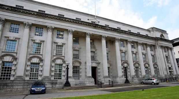 An accountant accused of keeping a Nigerian woman with the mental age of a four-year-old as domestic slave in Belfast must remain in custody, a High Court judge ruled on Wednesday.