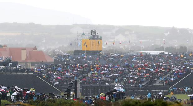 Crowds shielding themselves from the rain (Niall Carson/PA)