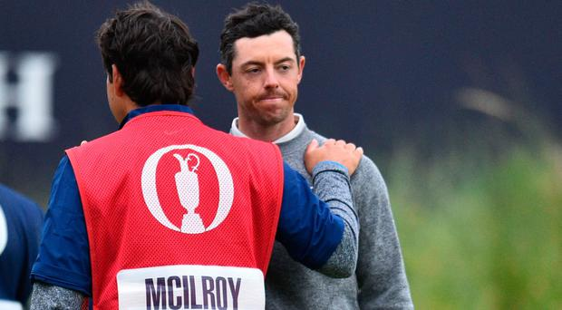 A disconsolate Rory McIlroy is comforted by his caddy at the 18th green