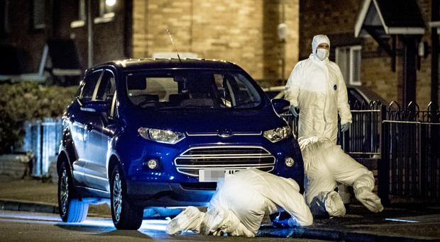 Forensic officers examine a car on the Springfield Road