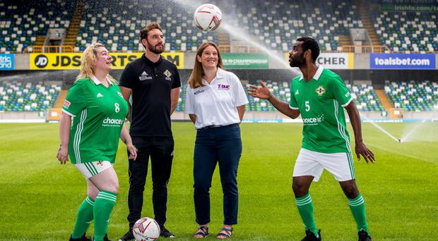 Janette Kelly and Ahmed Elneel are watched by Justin McMinn of Street Soccer NI and Katherine Hill from the Department for Communities