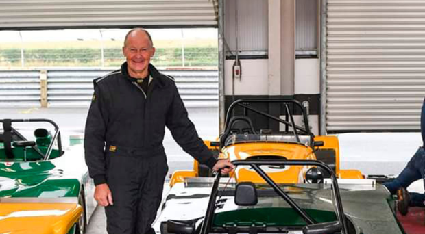 Dr Paul Conn posing beside one of his racing cars