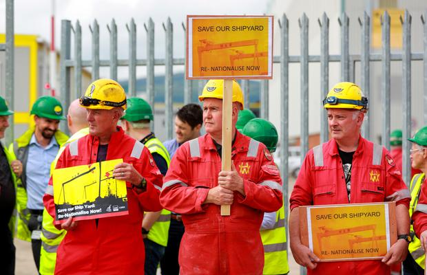 Shipyard workers stage a protest outside the gates of Harland & Wolff yesterday