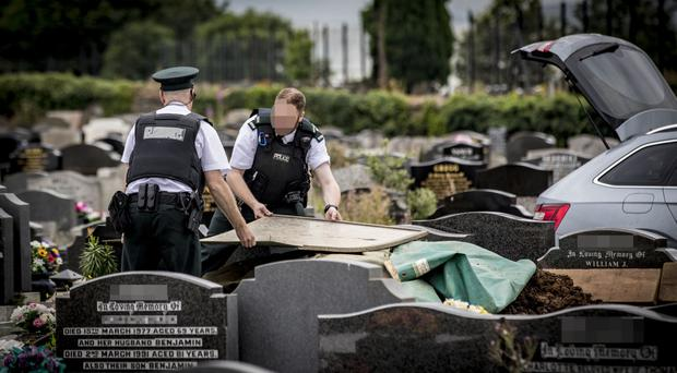 Officers investigate the grave at Seagoe Cemetery
