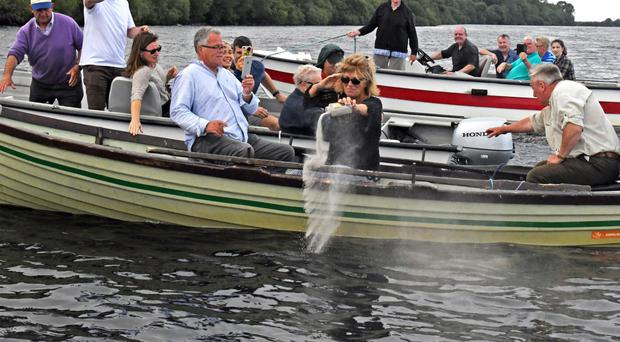 Kelly, the widow of Paul Eccleston, scatters his ashes as family and friends took a flotilla of four boats out on Lough Melvin