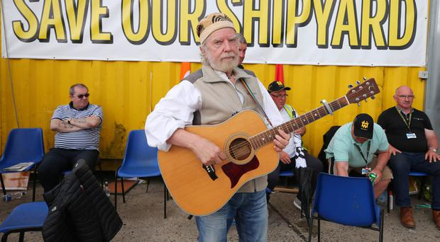 Local folk singer Tommy Sands visits Harland & Wolff and performs for the workers who are continuing their protest
