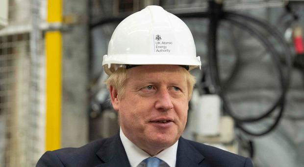 Prime Minister Boris Johnson gestures during his visit to the Fusion Energy Research Centre at the Fulham Science Centre in Oxfordshire yesterday