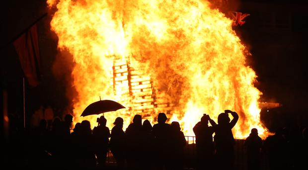 Crowds watch as a bonfire is lit in the New Lodge area of Belfast (PA)
