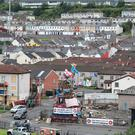 Masked youths on top of a controversial bonfire in the Bogside estate in Derry