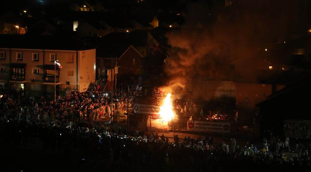 The main bonfire is lit in the Bogside area of Londonderry (Niall Carson/PA)