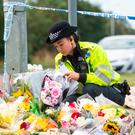 A police officer arranges flowers left near the scene where Thames Valley Police officer PC Andrew Harper was killed