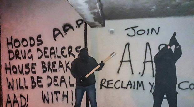 Action Against Drugs members in front of the graffiti in the New Lodge