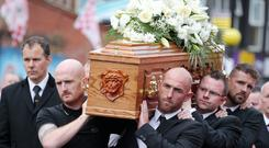 Ryan Catney and Barry Johnston carry Tommy's coffin