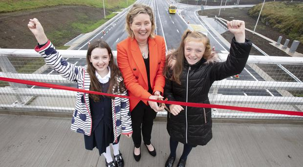 Department for Infrastructure Permanent Secretary Katrina Godfrey officially opens the first phase of A6 Randalstown to Castledawson scheme with a little help from Juliet Murray and Grace O'Boyle, pupils at St Oliver Plunkett Primary School