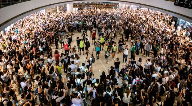 Protesters sing songs and shout slogans after gathering at the IFC Mall in Hong Kong yesterday