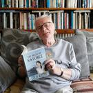Colin McAlpin at home with one of his books
