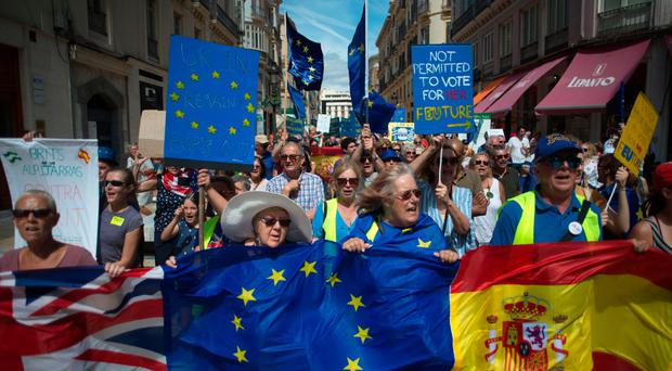 British nationals wave EU and Spanish flags as they take part in a protest against Brexit in Malaga yesterday