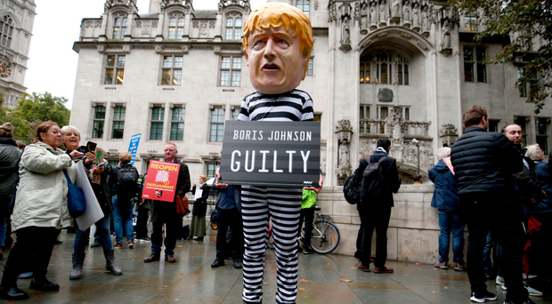 A man wearing a giant Boris Johnson mask, dressed as a prisoner, outside the Supreme Court